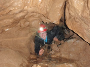 Squeezing through a small, muddy, underground hole!