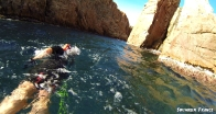 Swimming into the narrrow channel with high rocks on both sides